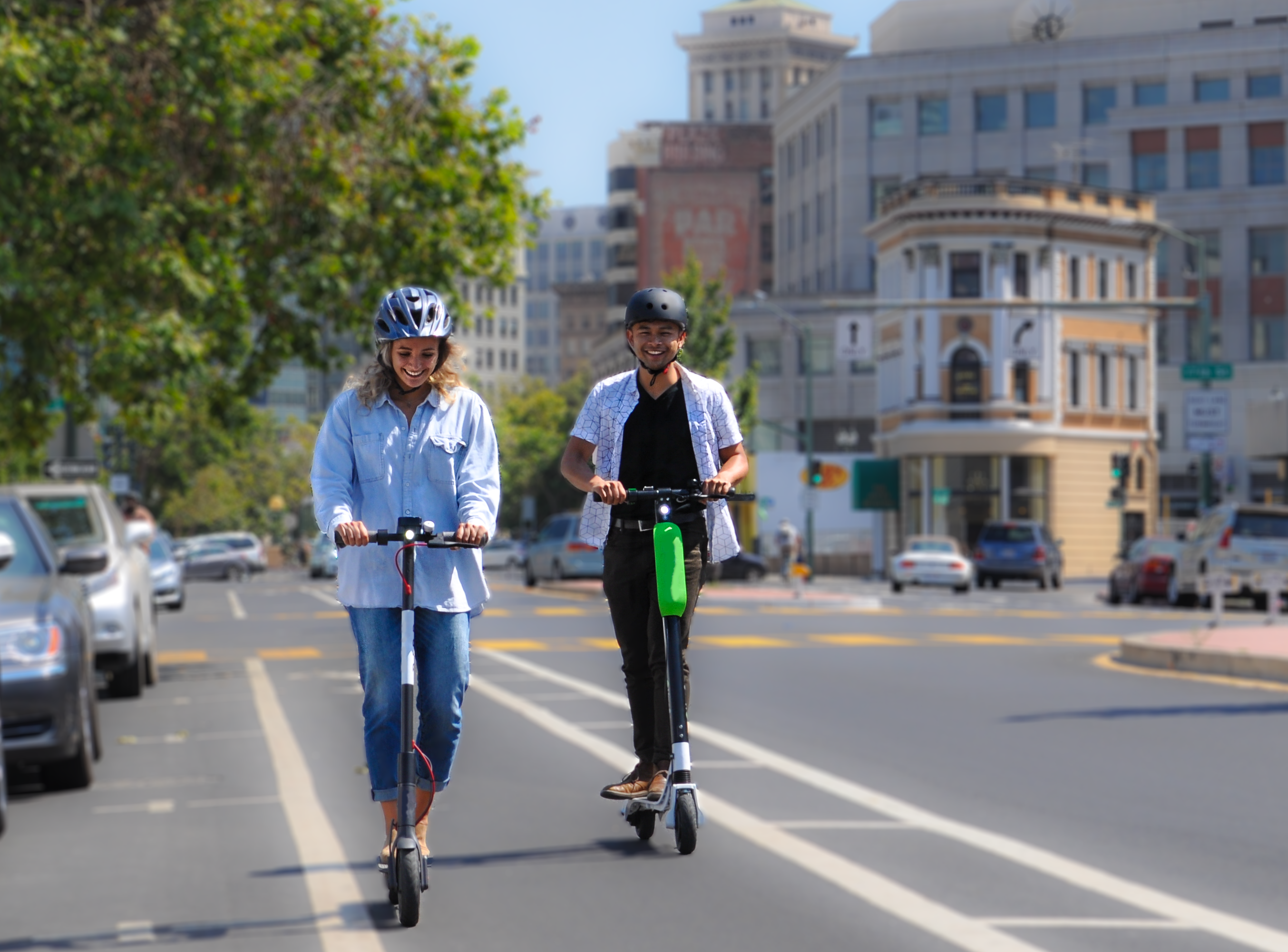 Two people riding scooters